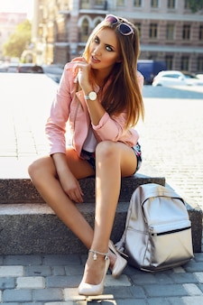 Schöne junge frau, die modische kleidung, handtasche, sonnenuhren der silbernen uhren trägt, die unten in der stadt sitzen. helles make-up, brauner körper, lange beine