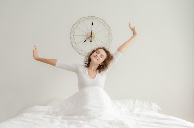 Schöne junge frau, die morgens in ihr bett aufwacht und ausdehnt