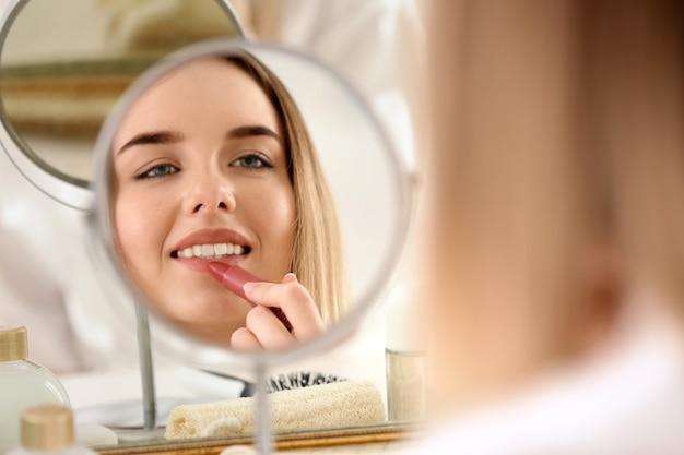 Schöne junge frau, die morgens make-up aufträgt