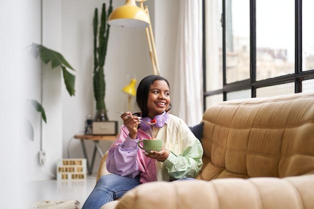 Schöne junge frau, die müsli in einer schüssel isst, die zu hause auf dem sofa sitzt.