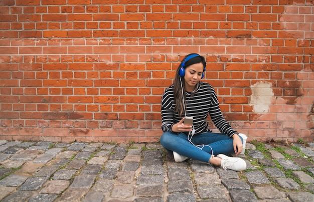 Schöne junge frau, die musik hört und ihr smartphone benutzt. technologiekonzept. städtische szene.