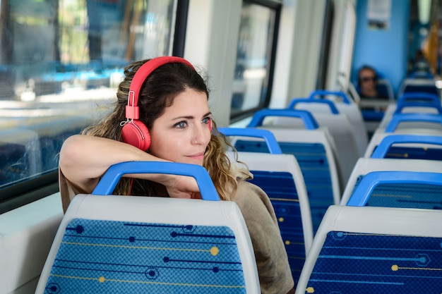Schöne junge frau, die musik in einem zug hört.