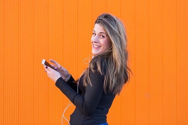 Schöne junge frau, die musik mit kopfhörern hört und spaß über freizeitkleidung der orange wand hat