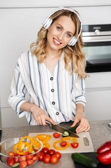 Schöne junge frau, die musik mit kopfhörern in der küche hört und frischen salat macht