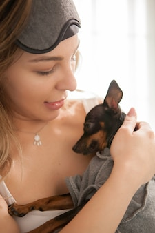 Schöne junge frau, die nach dem aufwachen ihren kleinen hund hält.