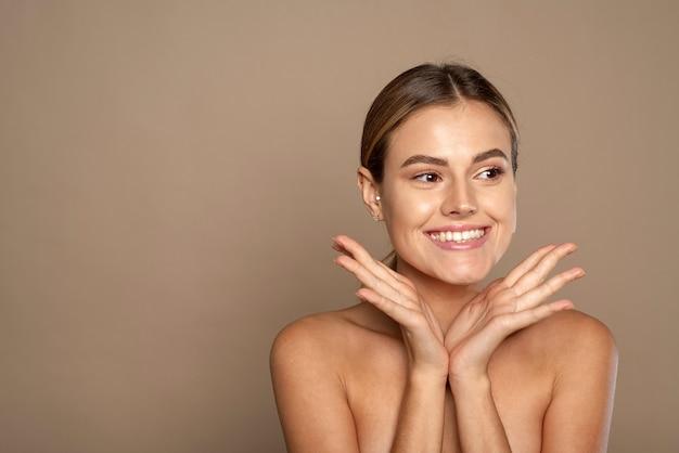 Schöne junge frau, die nach fantastischer gesichtsbehandlung lächelt. glückliche schönheitsdame aufgeregt nach spa-behandlung auf hintergrund mit kopienraum isoliert.