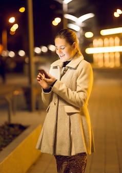 Schöne junge frau, die nachts smartphone auf der straße benutzt