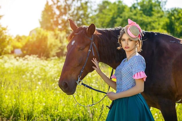 Schöne junge frau, die nahe bei einem pferd in der natur steht.