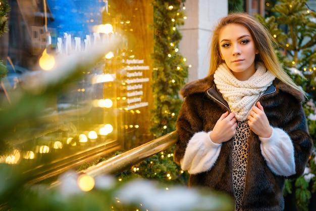 Schöne junge frau, die nahe dem fenster auf der straße im winter, feststimmung steht