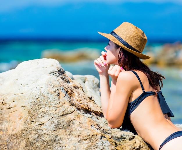Schöne junge frau, die nahe großem stein auf dem strand steht und das meer in griechenland betrachtet