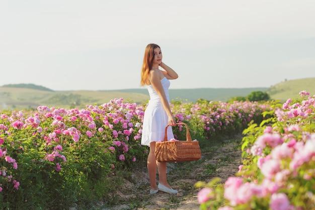 Schöne junge frau, die nahe rosen in einem garten aufwirft,