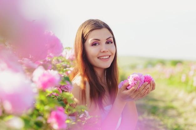 Schöne junge frau, die nahe rosen in einem garten aufwirft.