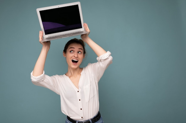 Schöne junge frau, die netbook-computer hält und nach oben schaut und sagt, wow trägt weißes hemd