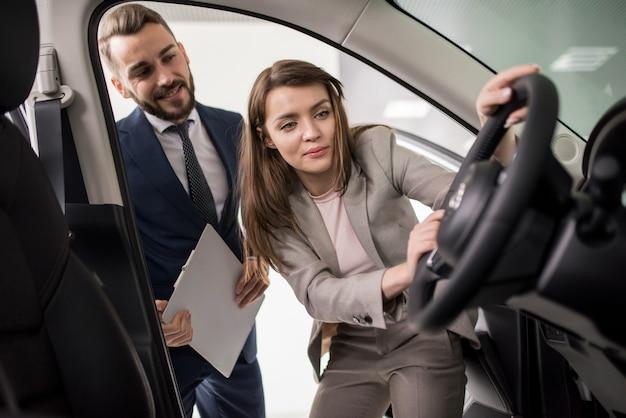 Schöne junge frau, die neues auto kauft