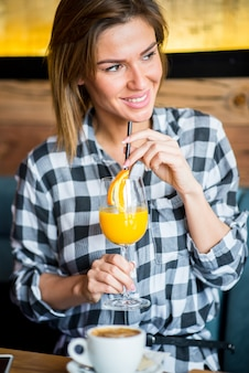 Schöne junge frau, die orangensaft trinkt
