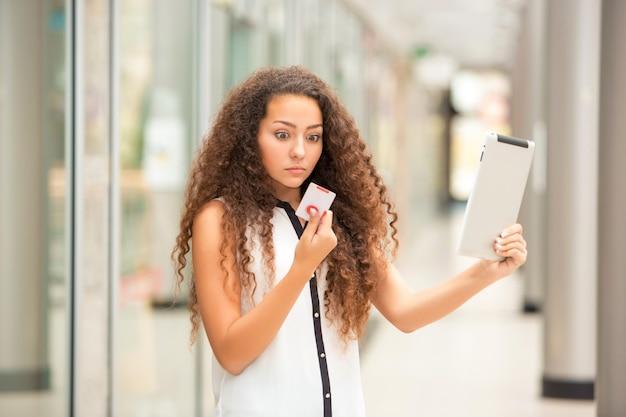 Schöne junge frau, die per kreditkarte für das einkaufen zahlt