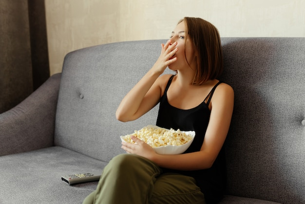 Schöne junge frau, die popcorn isst, während sie eine fernsehshow sieht, die auf sofa zu hause sitzt. entspannungskonzept.