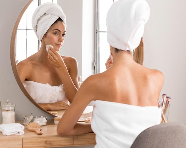 Schöne junge frau, die produkte verwendet und in den spiegel schaut