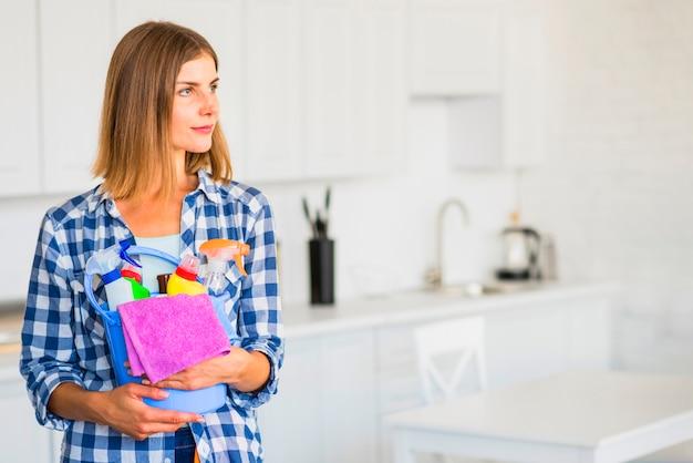Schöne junge frau, die reinigungsausrüstungen im eimer hält