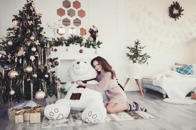 Schöne junge frau, die riesigen teddybär nahe weihnachtsbaum umarmt