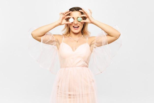 Schöne junge frau, die rosa fadenscheiniges kleid trägt, das macarons auf ihrem gesicht anstelle von augen aufwirft und hält