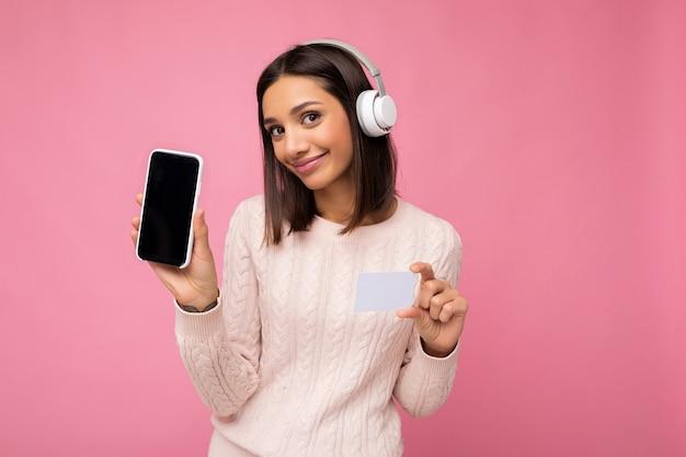 Schöne junge frau, die rosa lässigen pullover lokalisiert über rosa hintergrundwand trägt