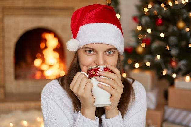 Schöne junge frau, die roten hut des weihnachtsmanns sitzt, der nahe kamin im wohnzimmer mit weihnachtsdekoration sitzt, dame, die heißes getränk trinkt, tasse mit beiden händen hält ,.