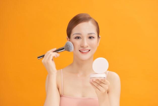 Schöne junge frau, die rouge auf ihre wange mit einem kosmetikpinsel und einem kleinen kompakten spiegel aufträgt