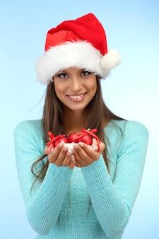 Schöne junge frau, die schnee mit weihnachtskugeln hält, auf blauem hintergrund