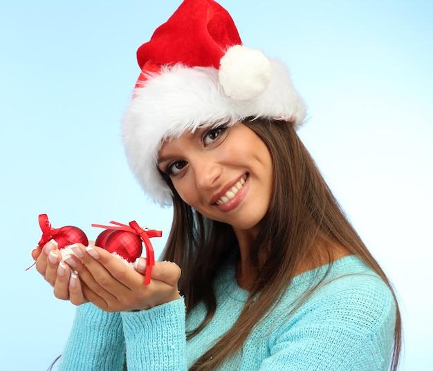 Schöne junge frau, die schnee mit weihnachtskugeln hält, auf blauer oberfläche