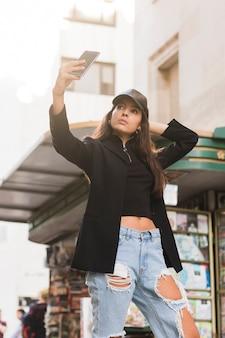 Schöne junge frau, die selfie am handy steht auf straße nimmt