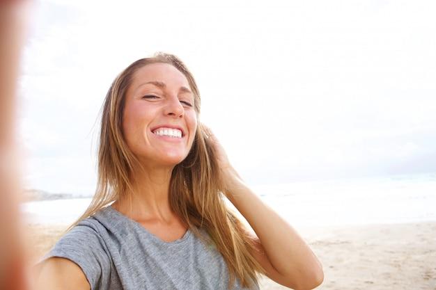 Schöne junge frau, die selfie am strand mit der hand im haar nimmt