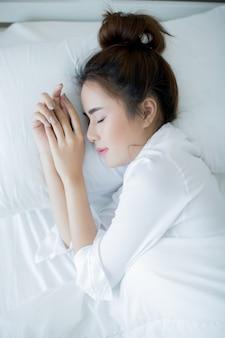 Schöne junge frau, die sich im bett hinlegt und schläft.