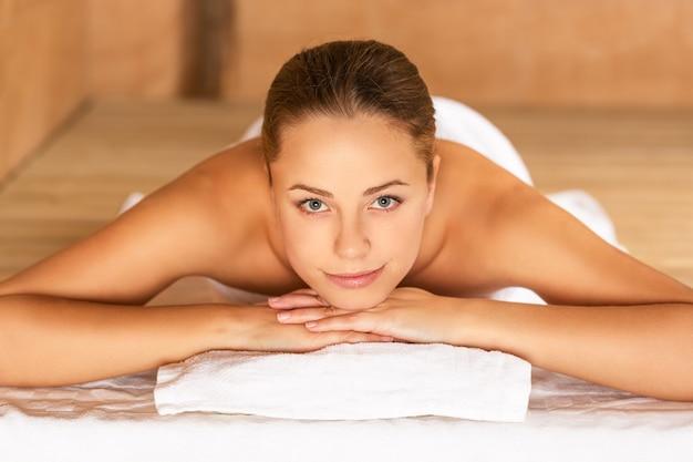 Schöne junge frau, die sich mit massage im beauty spa entspannt