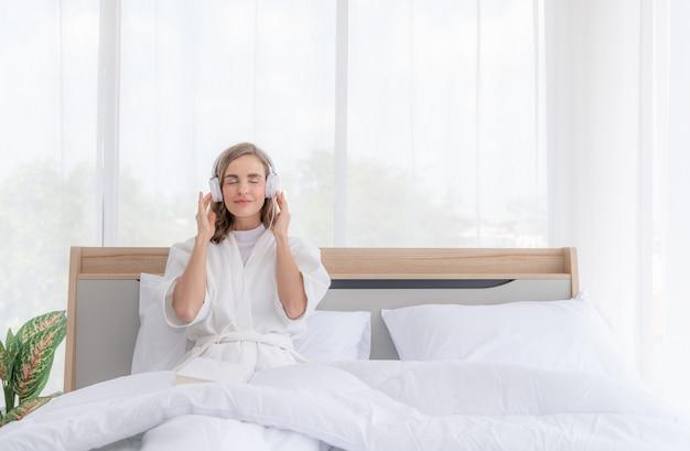 Schöne junge frau, die sich morgens das hören musik mit kopfhörern auf dem bett entspannt