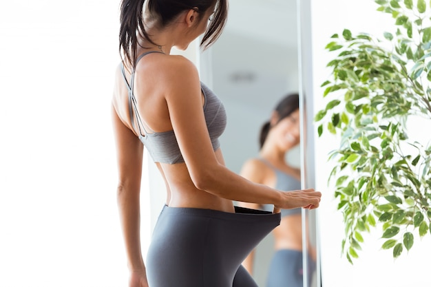 Schöne junge frau, die sich zu hause reflexion im spiegel betrachtet.