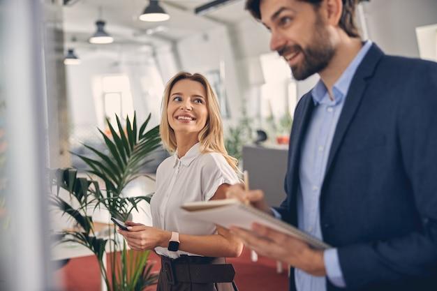 Schöne junge frau, die smartphone hält und lächelt, während ihr männlicher mitarbeiter in notizbuch schreibt
