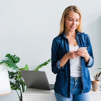 Schöne junge frau, die smartphone im büro verwendet