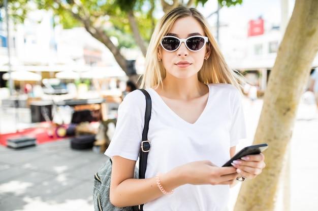 Schöne junge frau, die smartphone im freien in der sonnigen sommerstraße verwendet