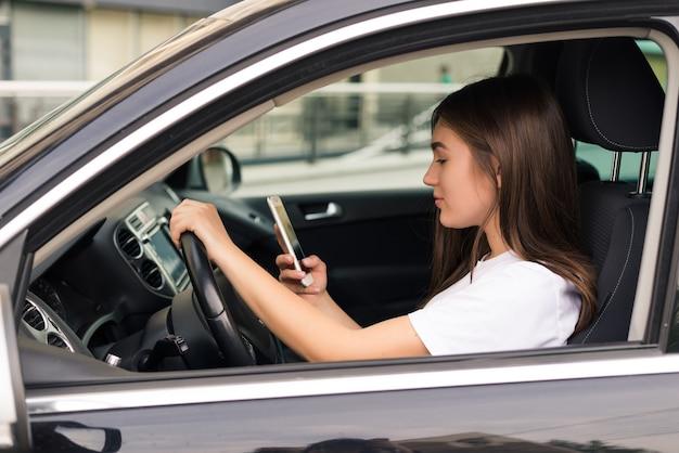 Schöne junge frau, die sms schreibt, während auto fährt.