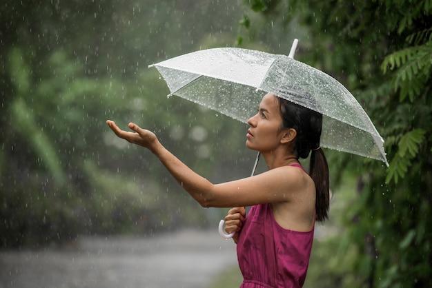 Schöne junge frau, die so traurig ist, wie sie ihre palme heraushält, um das regnen zu fangen