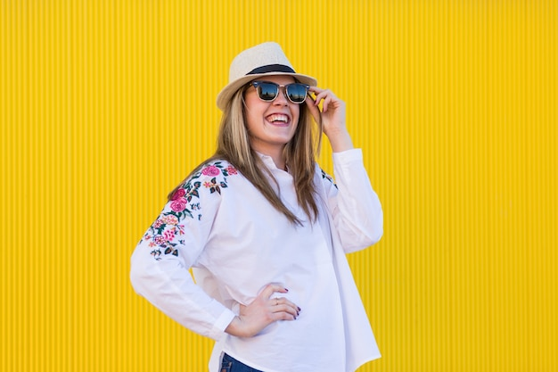 Schöne junge frau, die sonnenbrille und lächelnden gelben wand lebensstil hält