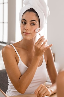 Schöne junge frau, die spa-produkte zu hause verwendet