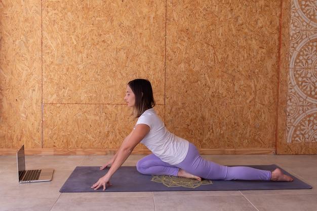 Schöne junge frau, die sportkleidung trägt, die übung auf purpurer yogamatte tut