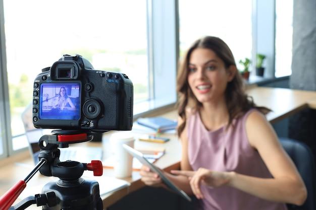 Schöne junge frau, die spricht und lächelt, während sie ein neues video für ihren blog macht.