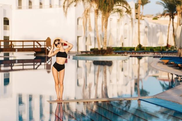 Schöne junge frau, die stilvollen schwarzen badeanzug, bikini, mädchen im urlaub, im urlaub, im resort, im schönen hotel trägt. tragen sie eine stilvolle sonnenbrille und einen strohhut in der hand.