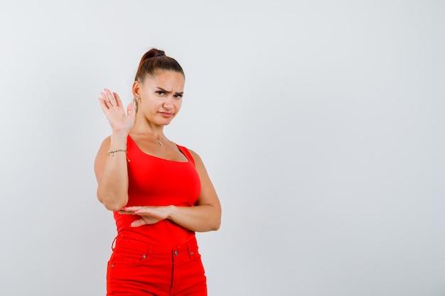 Schöne junge frau, die stoppgeste in rotem trägershirt, hosen zeigt und unzufrieden schaut, vorderansicht.