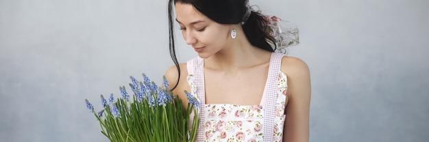 Schöne junge frau, die strauß der frühlingsblumen hält