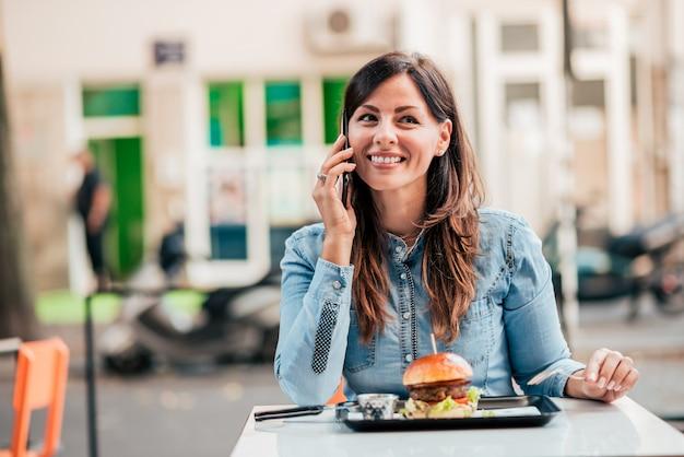 Schöne junge frau, die telefonisch im freienrestaurant spricht.