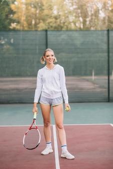 Schöne junge frau, die tennis spielt